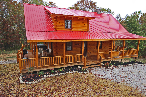 front of red roofed cabin, wrap around porch